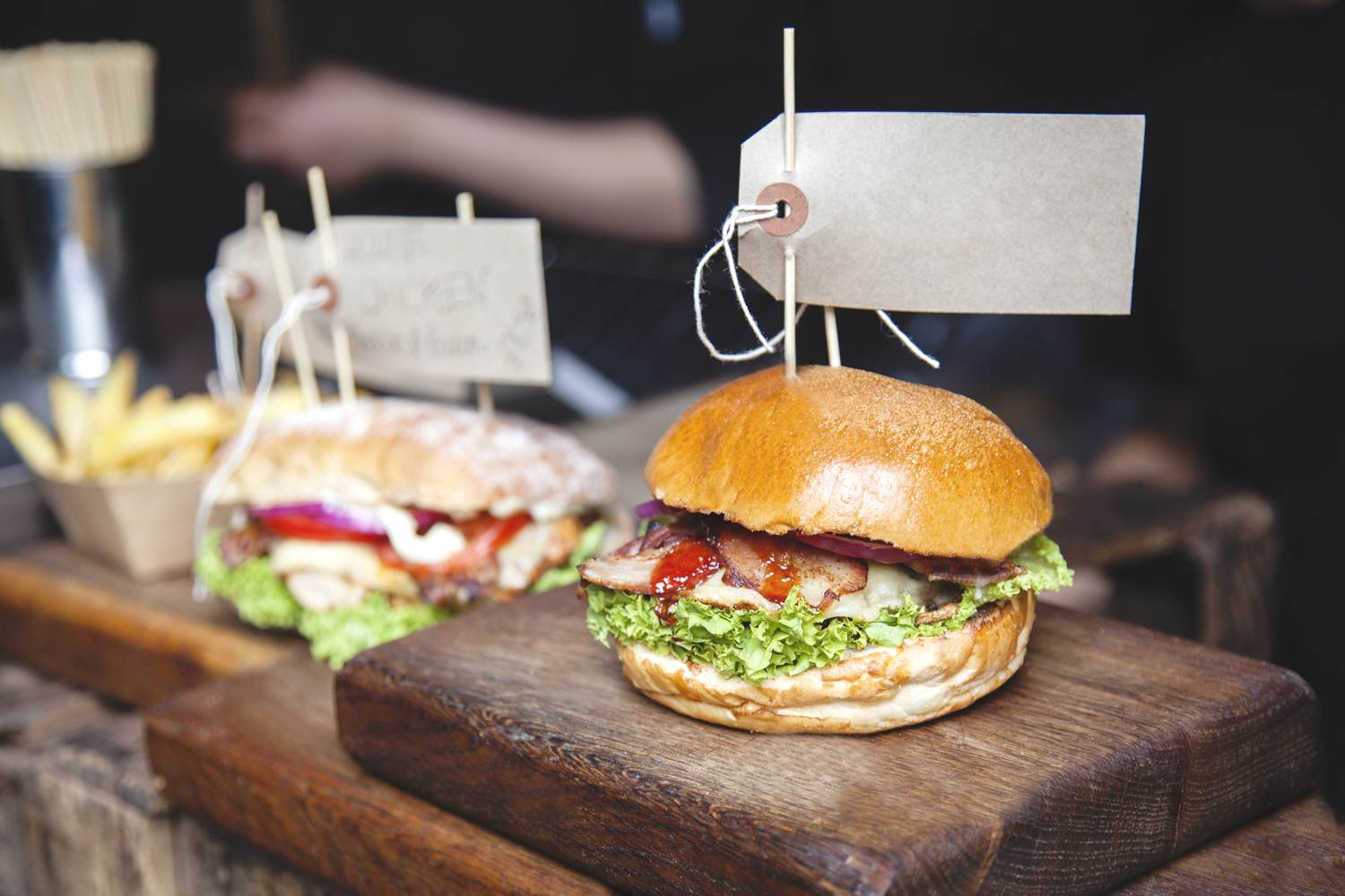 Street food burger speared with stick that has a blank price tag attached, on a wooden board, another burger and a portion of chips in the background