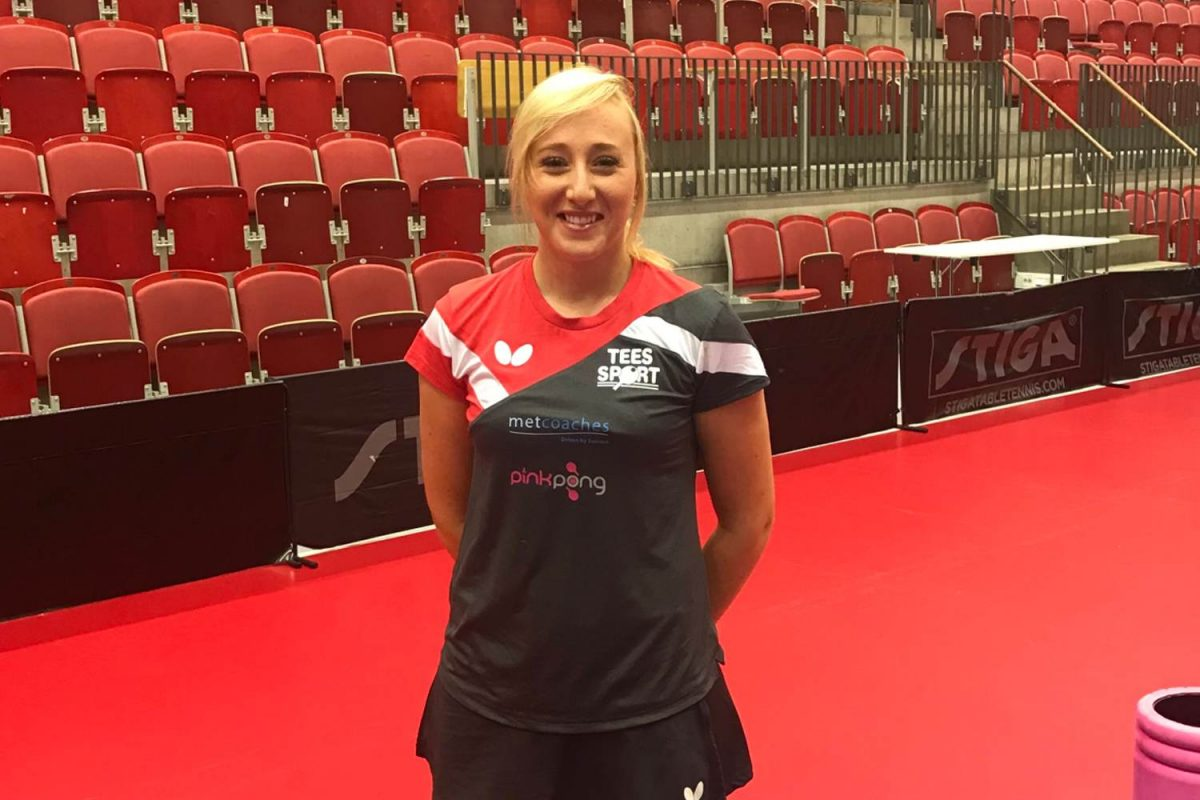 Charlotte Carey standing beside a table tennis table in the red version of her new season kit.