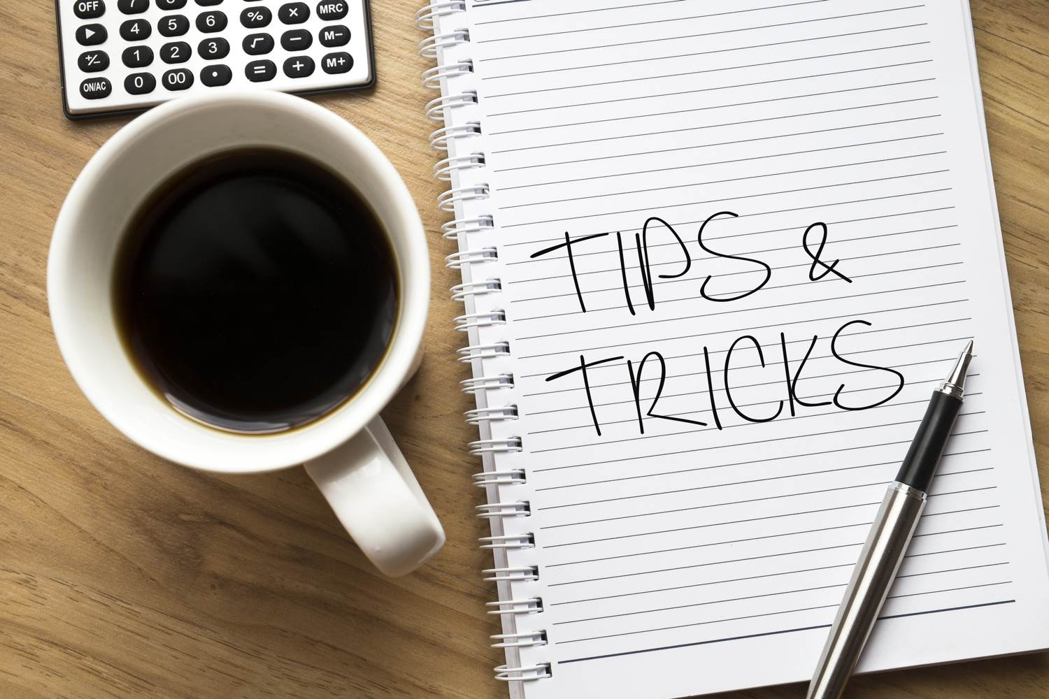 Tips and tricks for planning a corporate event - Tips and tricks written on notebook, cup of coffee on left side
